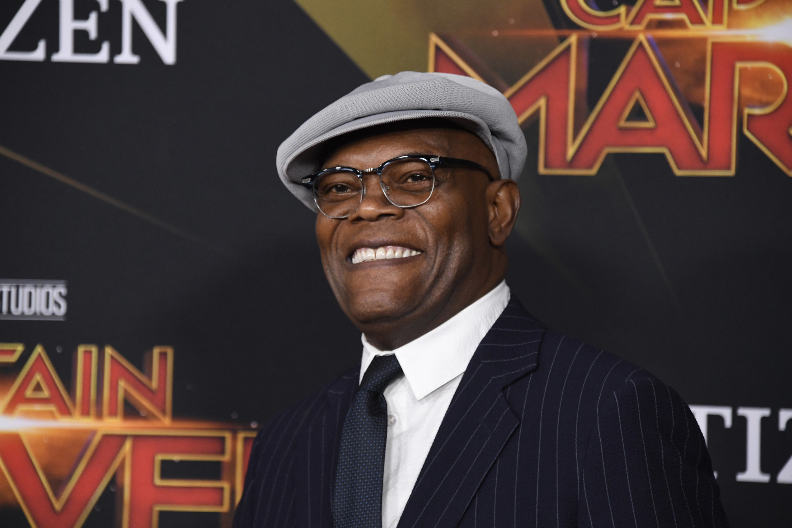 Samuel L. Jackson in a gray cap and suit and tie