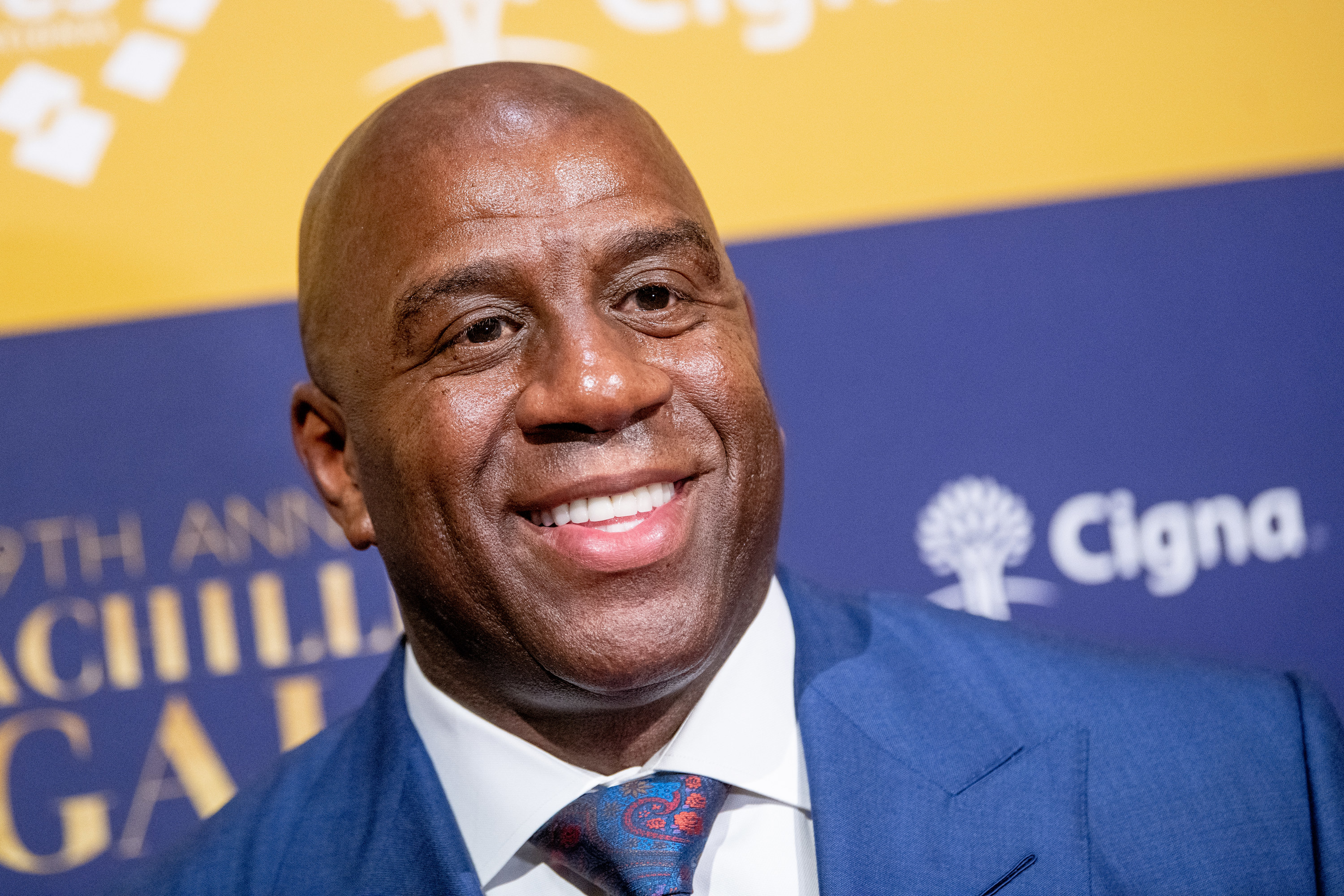 A smiling Magic Johnson in a suit and tie