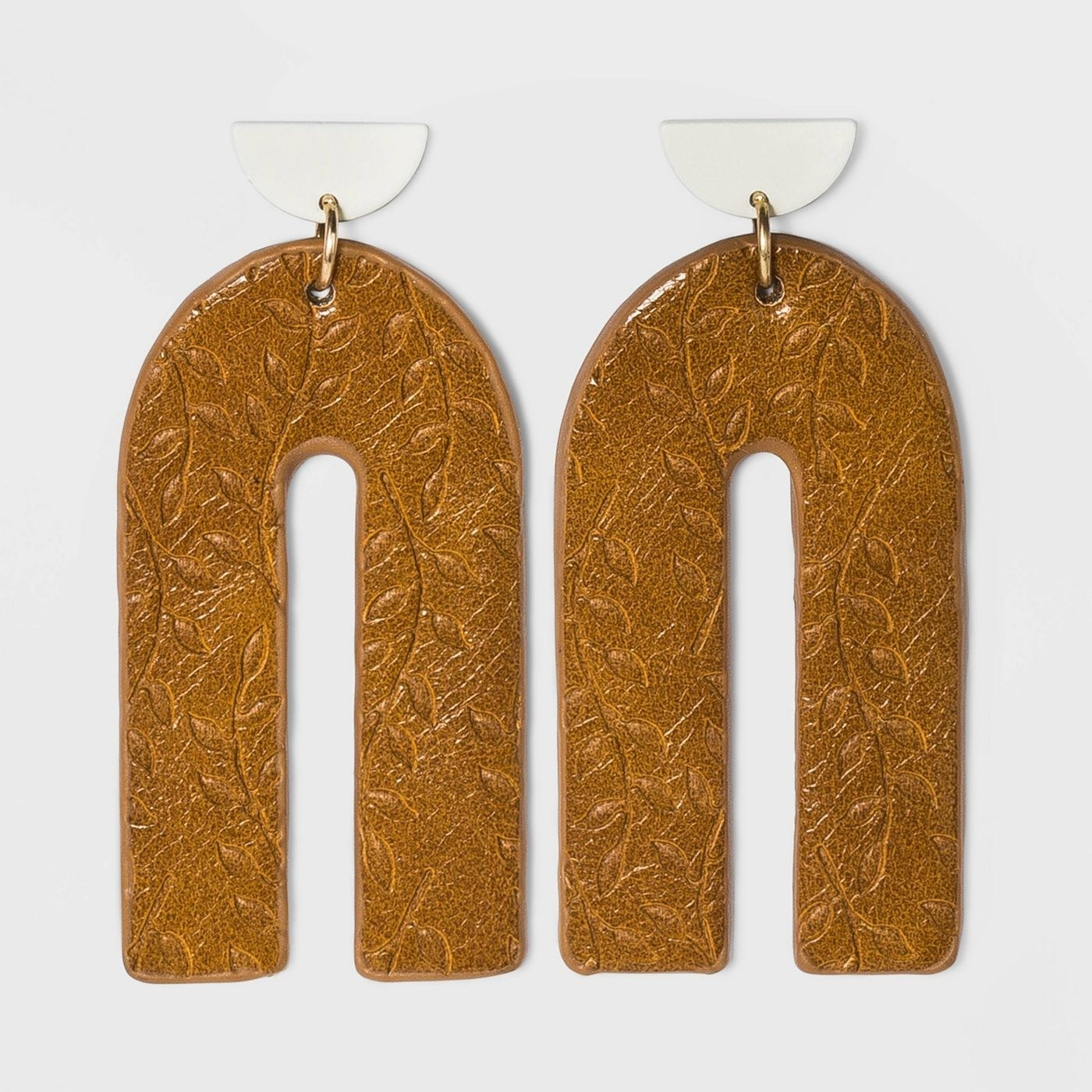 gold embossed u-shaped earrings with white half circle at the top
