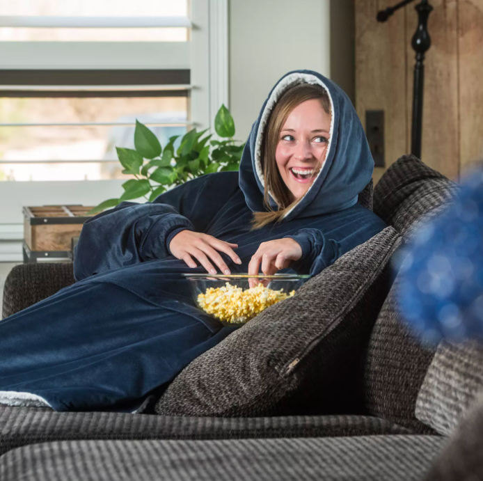A person curled up on their sofa, eating popcorn while wearing the hoodie