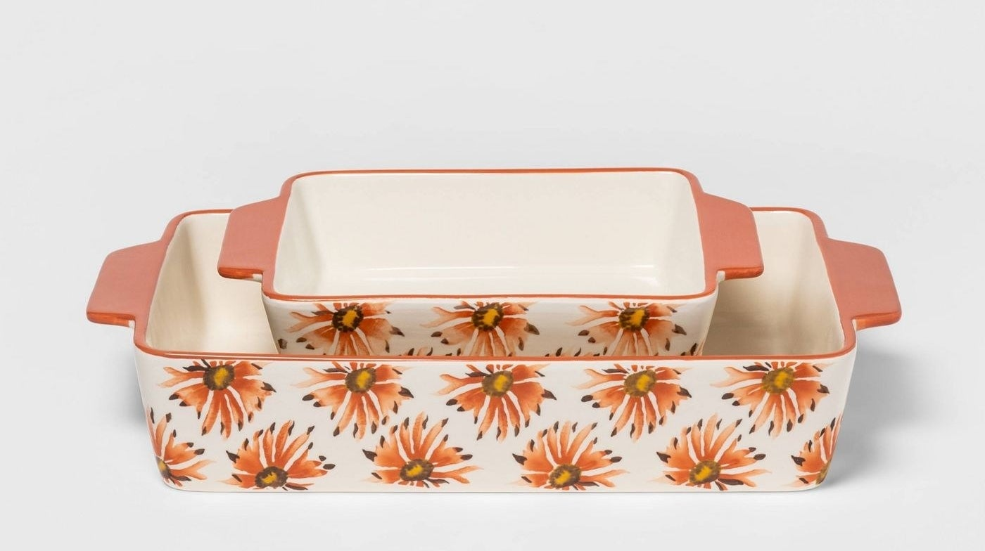 two rectangular baking dishes with peach handles and orange and brown flowers on the sides