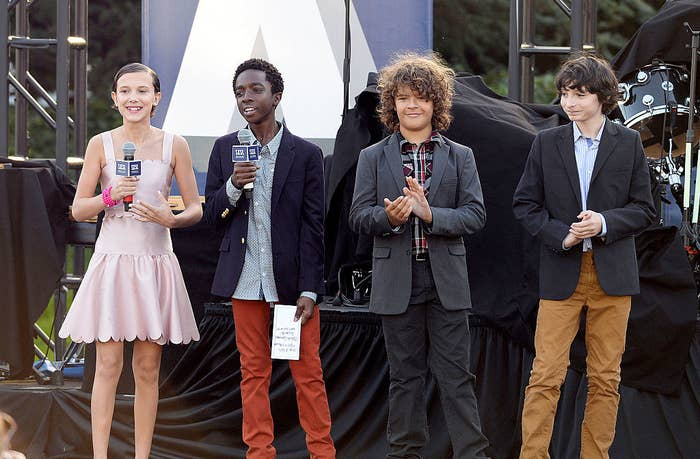 The cast speaking on a stage
