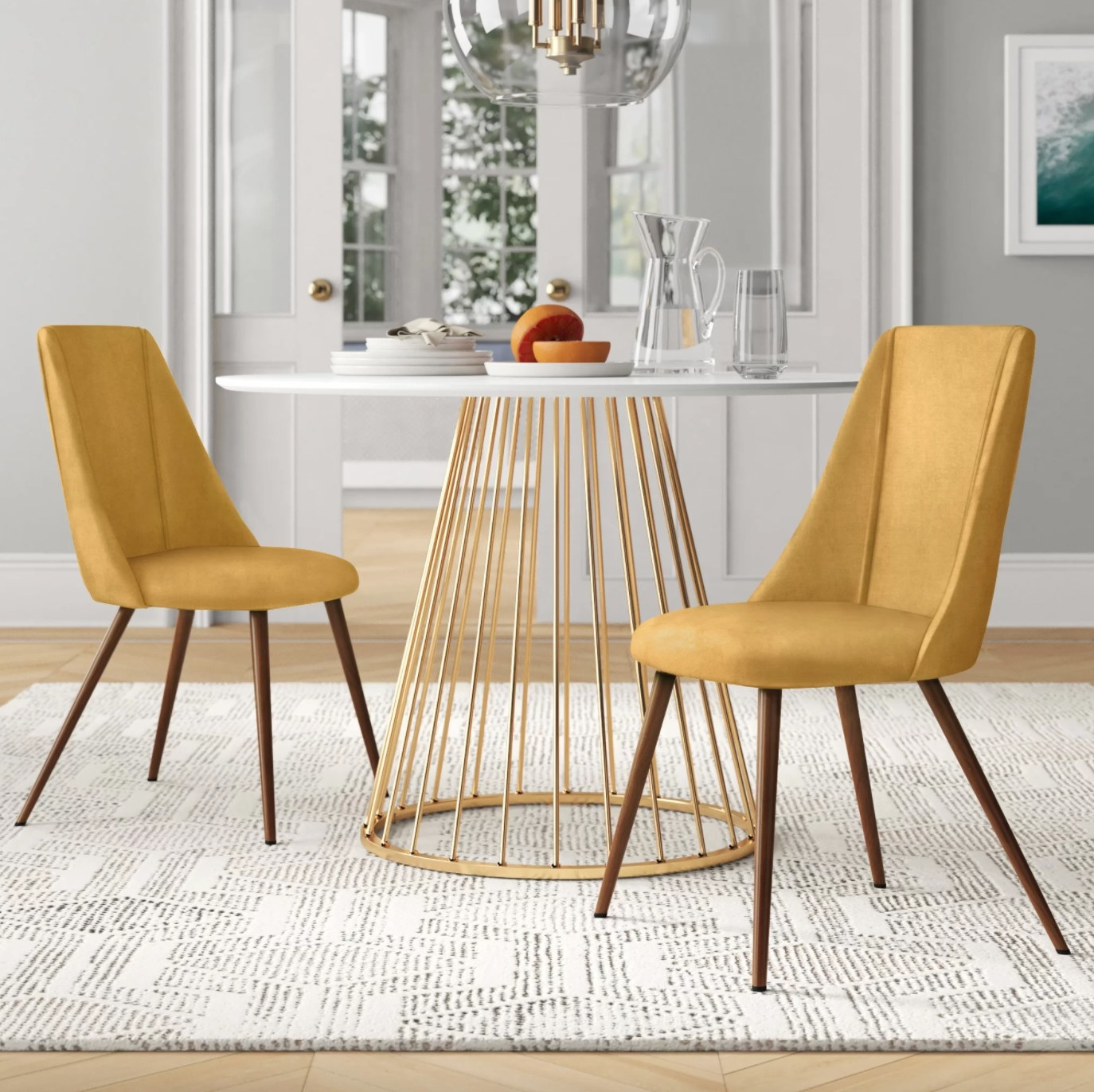 The set of two upholstered side chairs in yellow next to a round table with metal legs