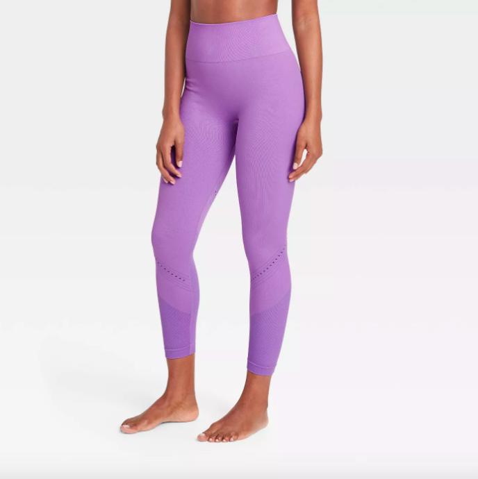 A model wearing the leggings in purple