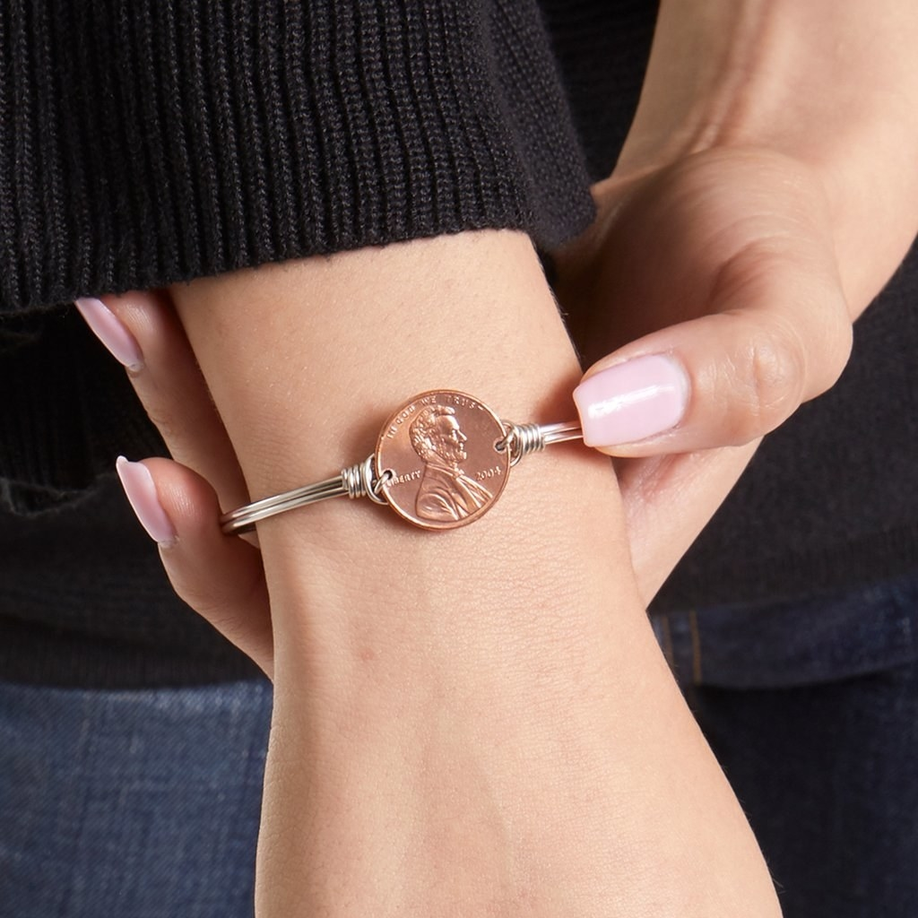 a thin silver band with a penny in the middle
