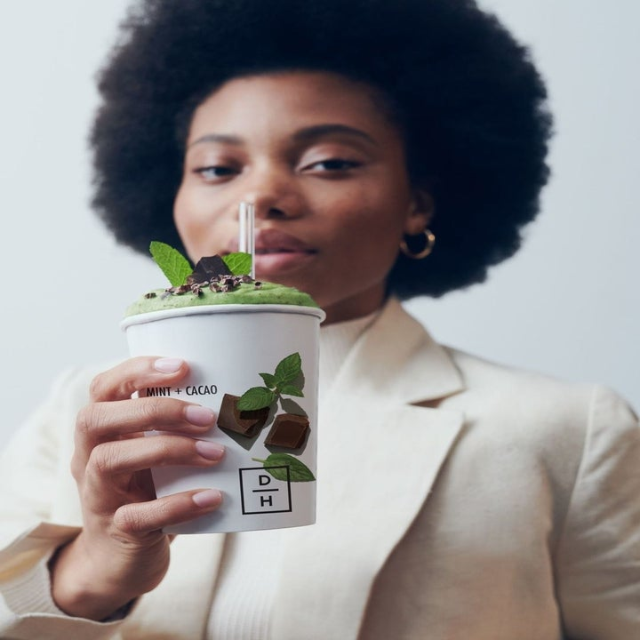 a model holding a mint smoothie