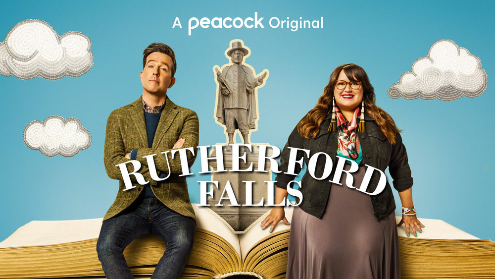Promotional graphic for Rutherford Falls featuring two characters sitting on an open books with clouds in the background