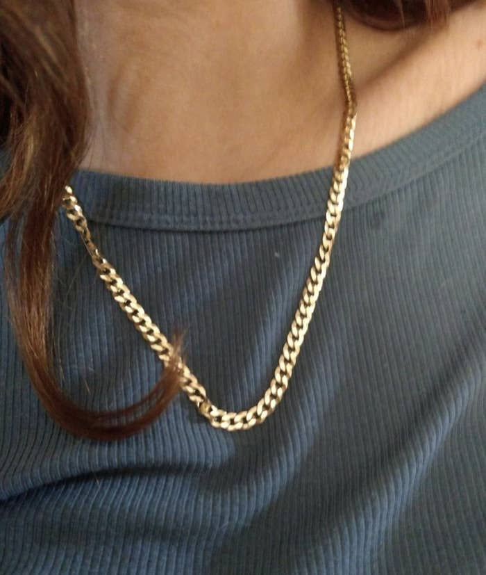 a person wearing a single gold chain