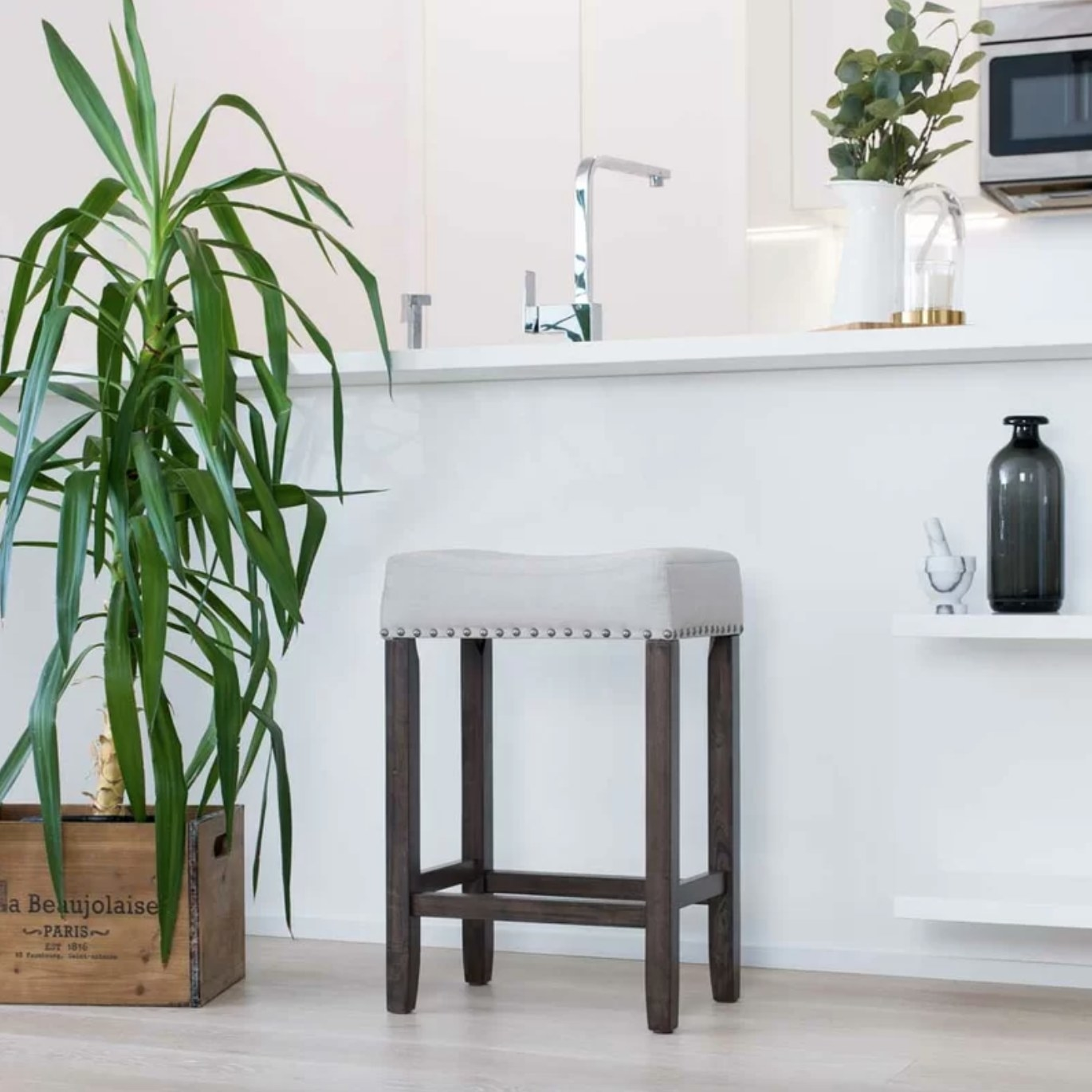 The bar and counter stool in gray with dark brown legs pulled up to a kitchen island