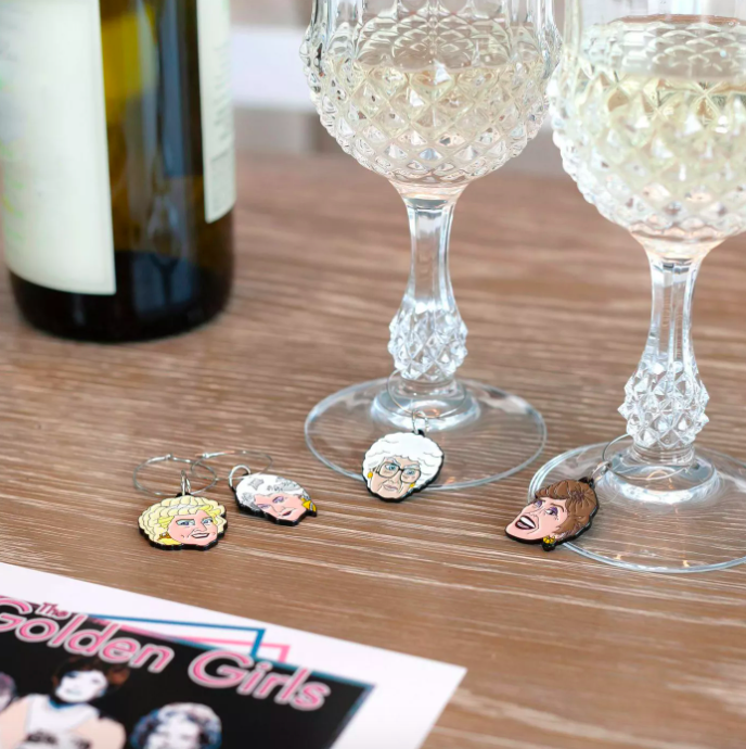The Golden Girls Wine Charms placed on glasses of wine and on a table