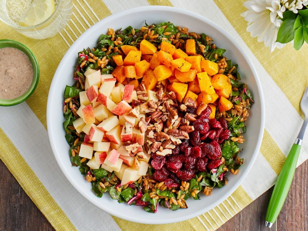 a harvest salad with apples, cranberries, walnuts, and squash over greens