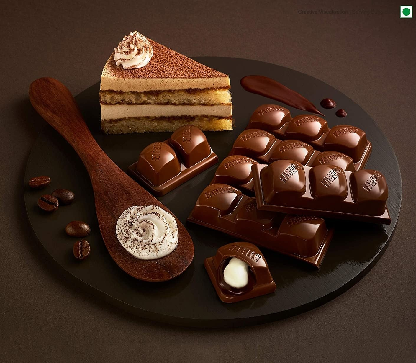 The chocolate bars placed on black plate with coffee beans, mascarpone dusted with cocoa powder, and a slice of tiramisu cake.