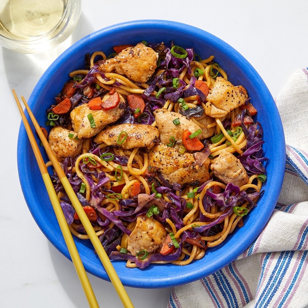 a bowl of chicken stir fry with carrots, cabbage, and noodles