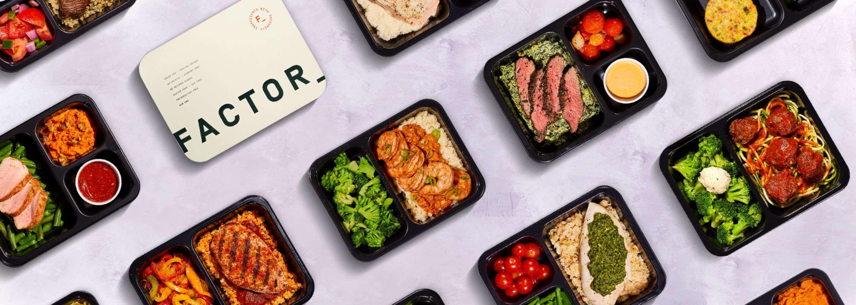 A bunch of pre-made meals in black containers