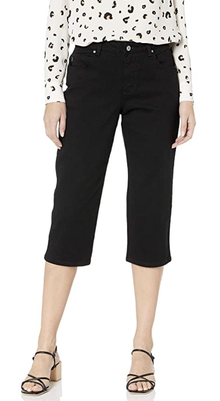 a model wearing black denim capri pants
