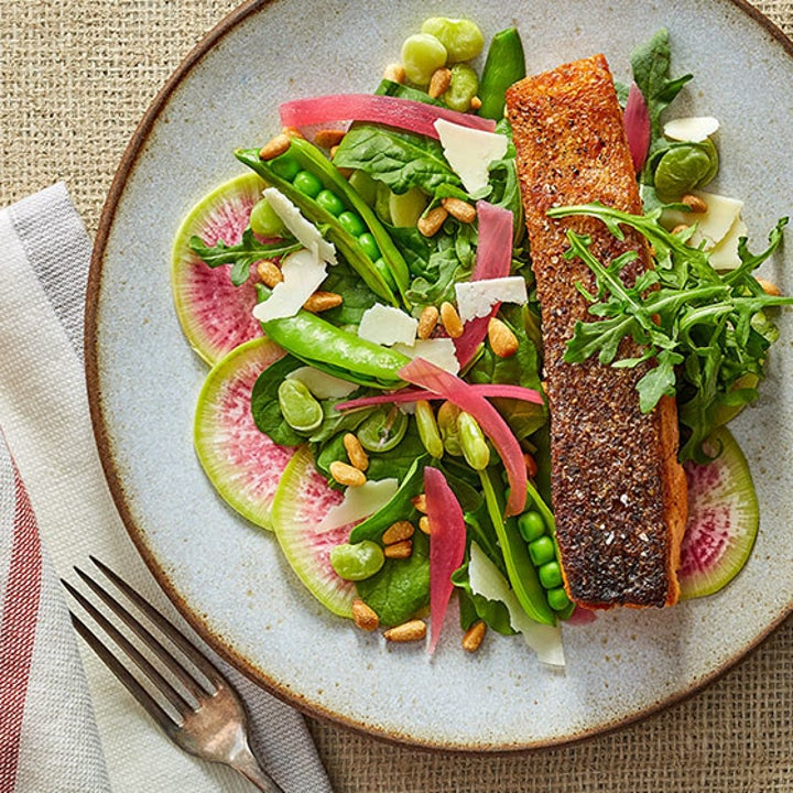 a plate of salmon, snap peas, and radish slices