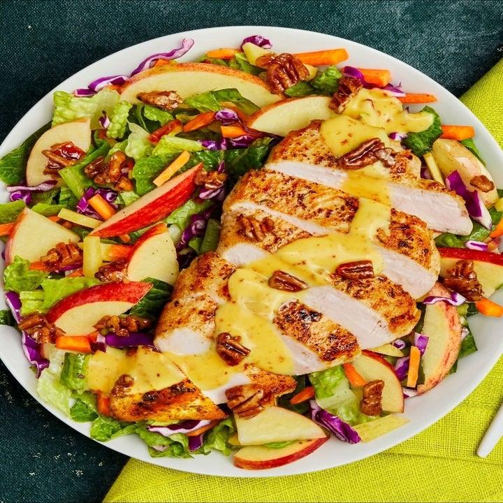grilled chicken served over a salad