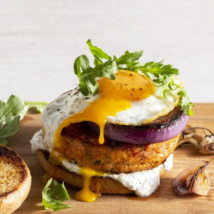 an open-face burger with an egg on top