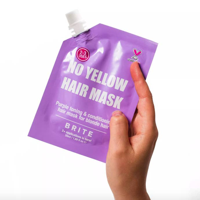 A hand holding up the pouch of Brite No Yellow Hair Mask