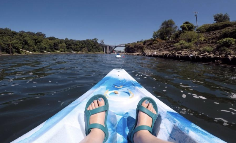 person's feet wearing the teal sandals with cross straps while sitting in a kayak on a river