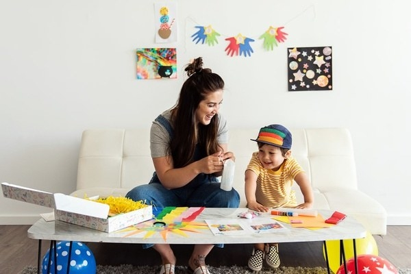 a child sitting on a couch next to an adult with craft supplies in front of them and completed crafts hanging on the wall