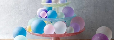 Dozens of sea glass balls in varying sizes displayed on a three tier treat tray