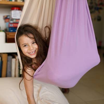 Child smiling while curled up inside the hanging fabric chair