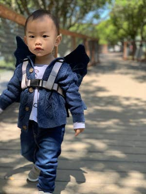 Child wearing dark wing harness attached with a buckle to their chest