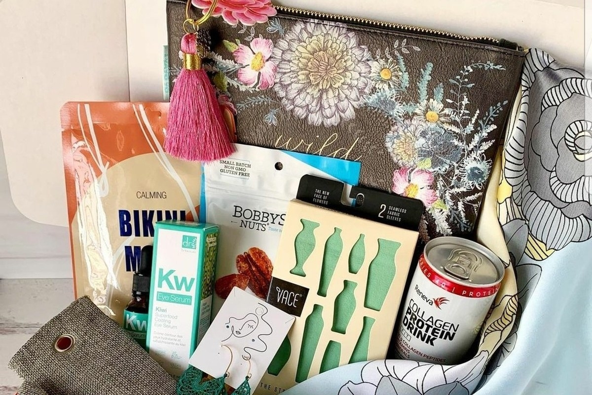 a box of wellness items including art, a protein shake, and skincare products