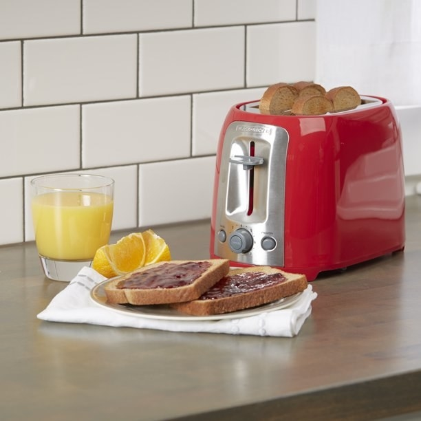 The toaster, which has a retro, streamlined design, in red