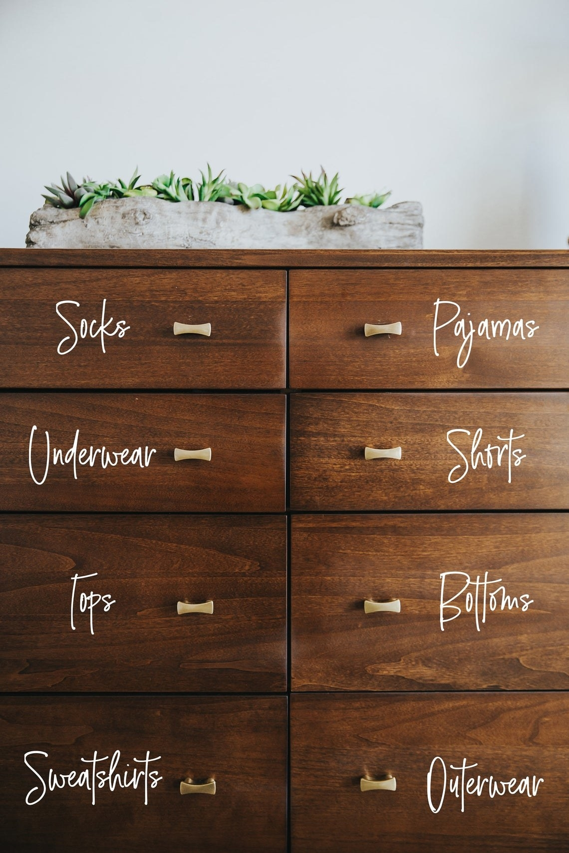 Dresser with written stickers on each drawer that say