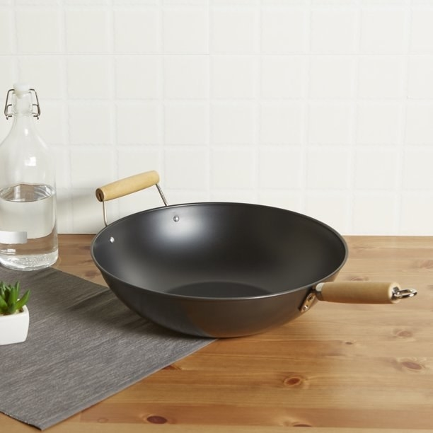 The wok, which has a steel body and two wooden handles extending out from the steel body