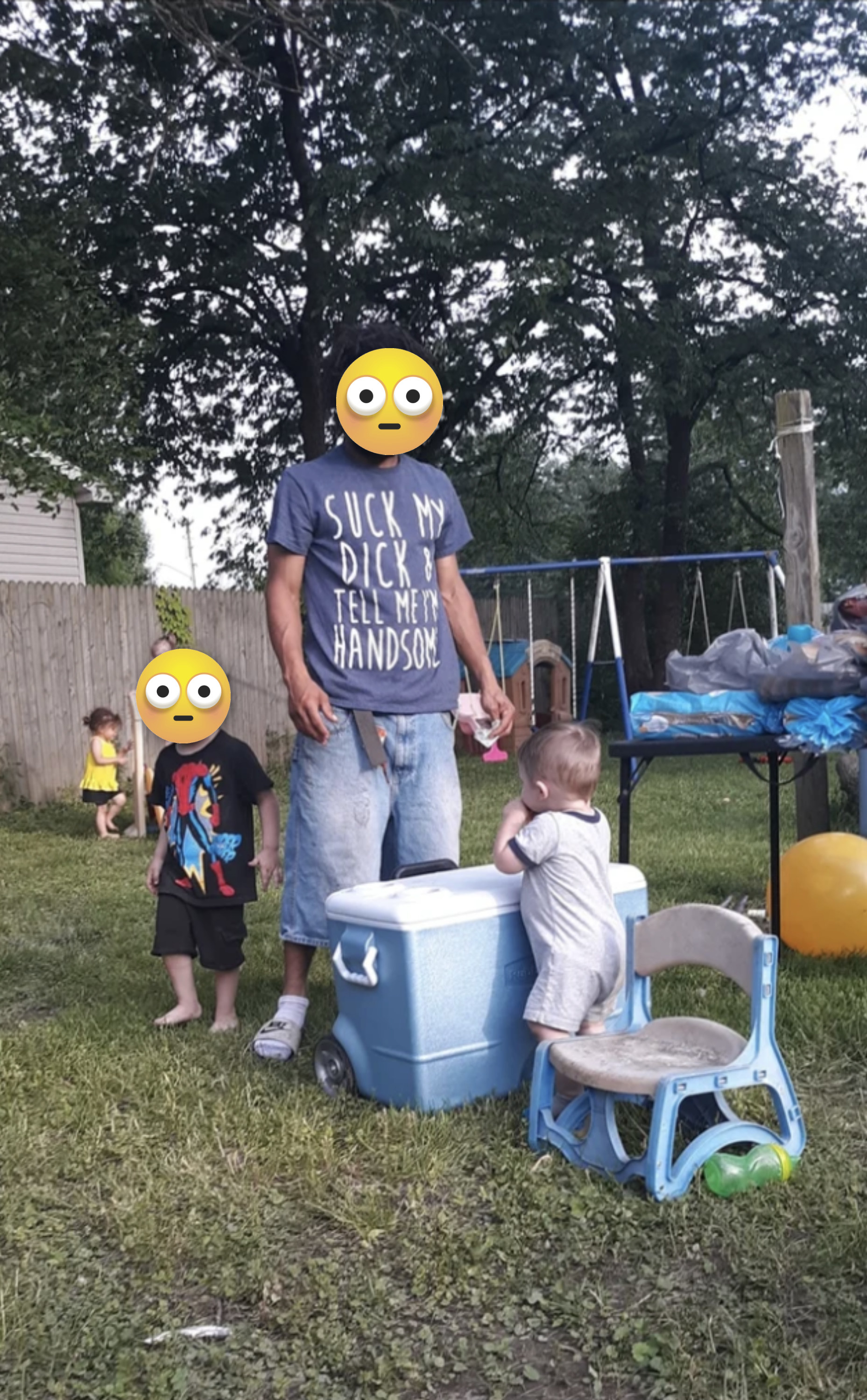 a man is surrounded by toddlers wearing a suck my dick t-shirt