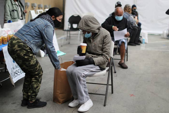 A woman in a hoodie sits on a metal chair outdoors and holds a cup of coffee after getting a COVID vaccine at a Los Angles shelter for people experiencing homelessness.