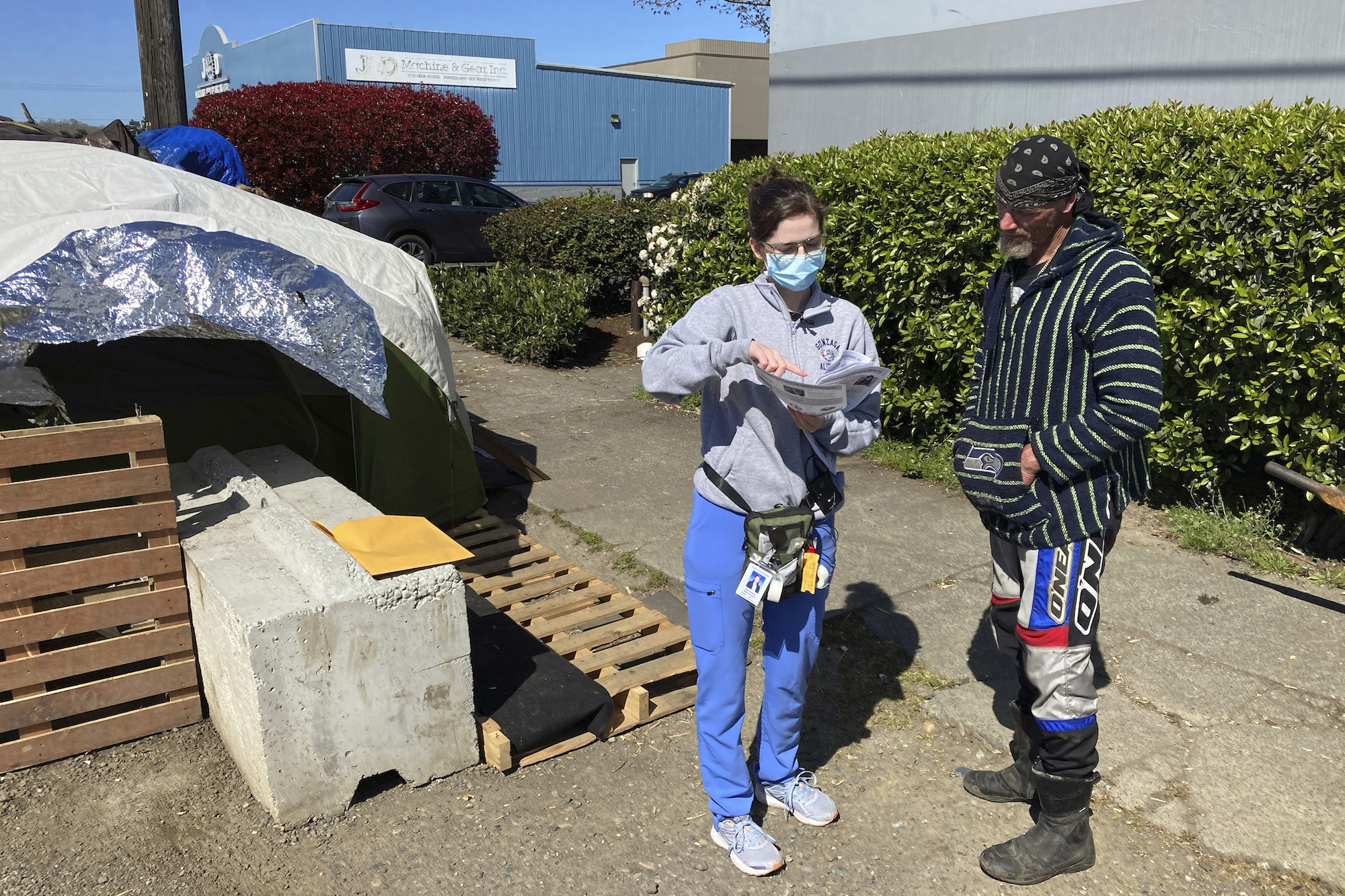 A woman in blue medical scrubs points to a piece of paper with COVID vaccine information while a man who lives at an encampment for people who are homeless looks on.