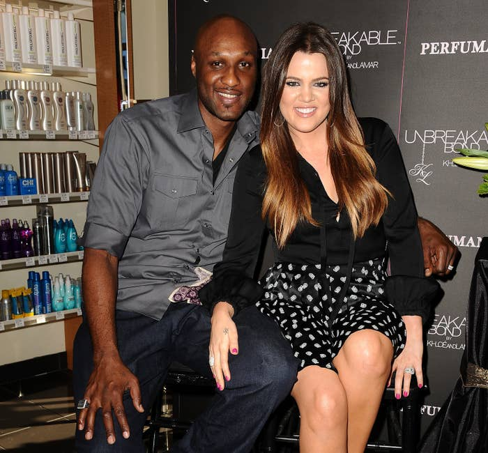 Lamar Odom and Khloe Kardashian sit next to each other at an event in 2012
