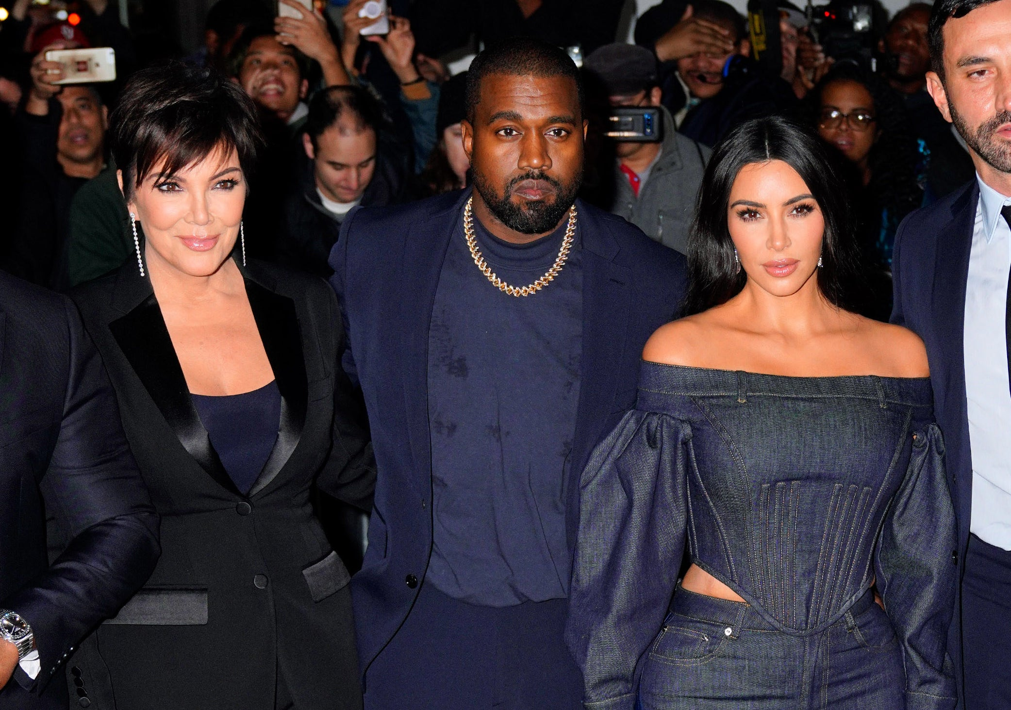 Kris, Kanye, and Kim walk together while being followed by camera