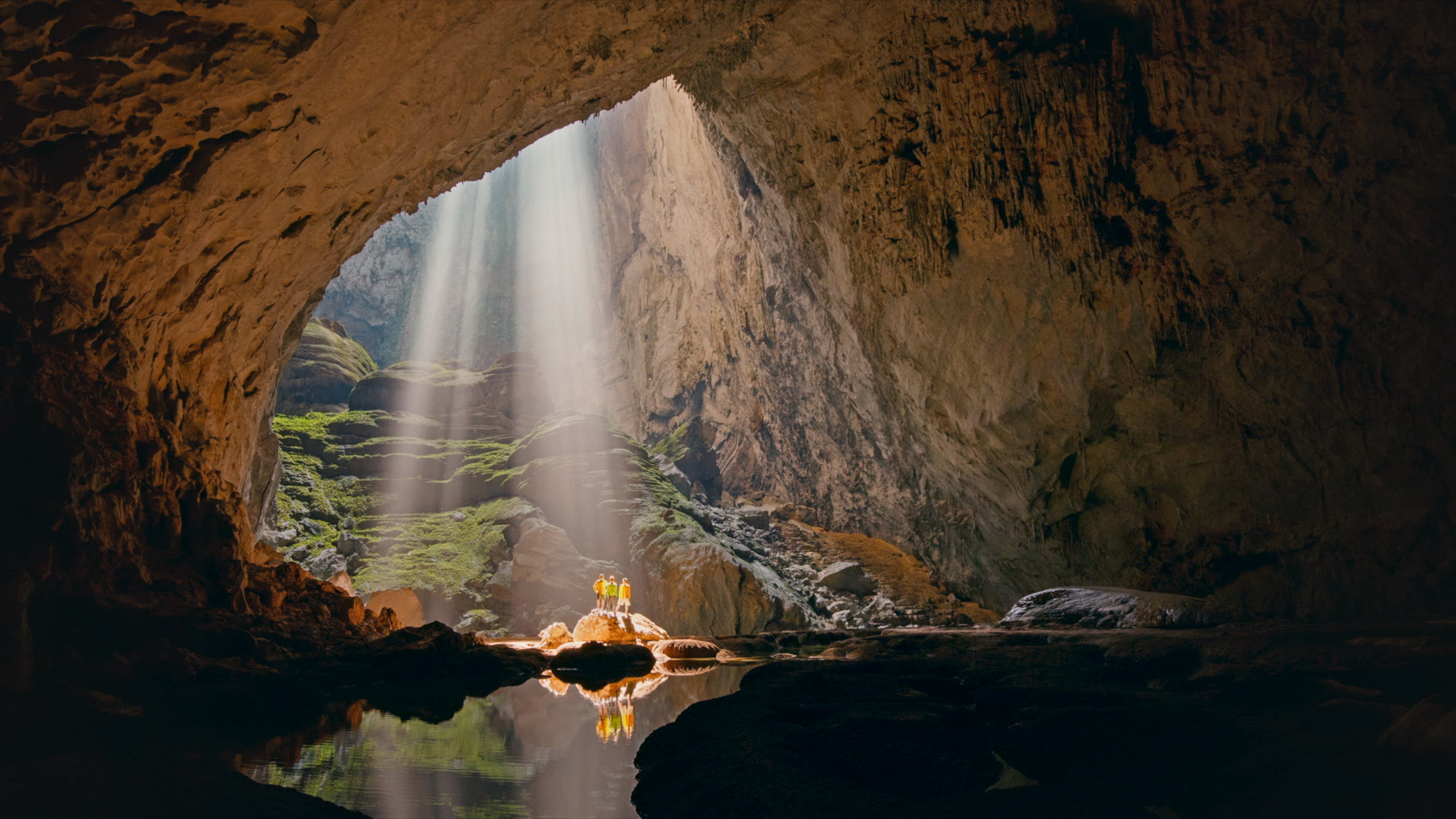 a cave with a light shining down onto three people