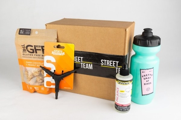 a water bottle, bag of snacks, and bike accessories next to the box