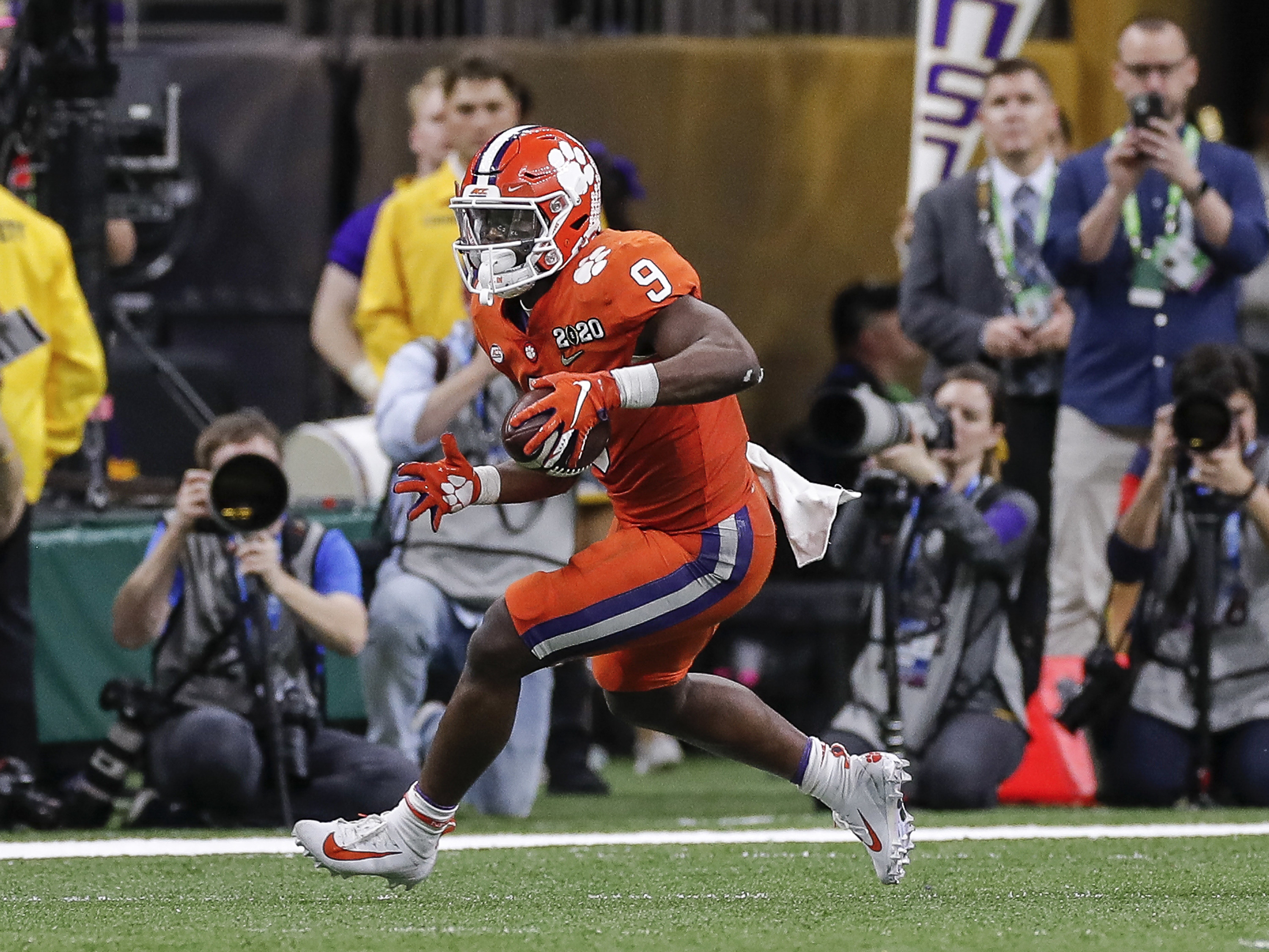 Travis Etienne running with the football