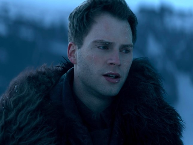 Matthias wears a fur-trimmed outfit and stands outside in a snowy area; he has a reddened face covered in frost