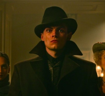 Kaz wears a hat and coat and stares straight ahead
