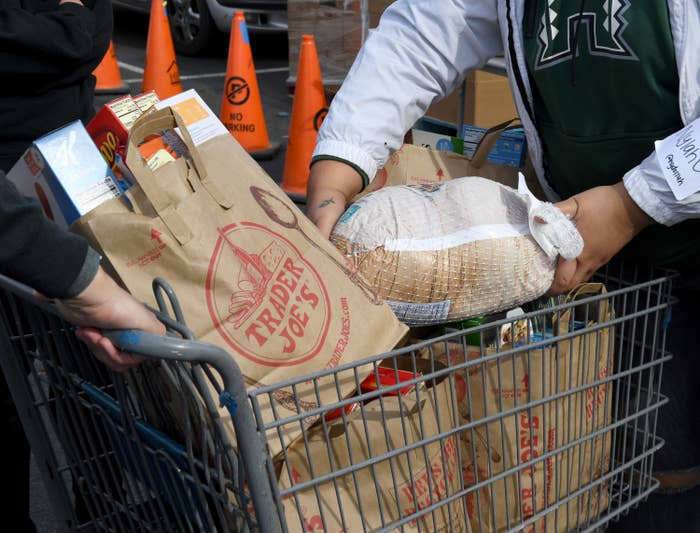 Shopping cart filled with groceries in Trader Joe's bags