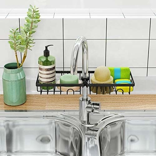 Black sink caddy with cleaning products on it.