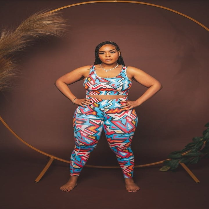model in bright pink, blue, orange, and white geometric print high-rise leggings and matching sports bra