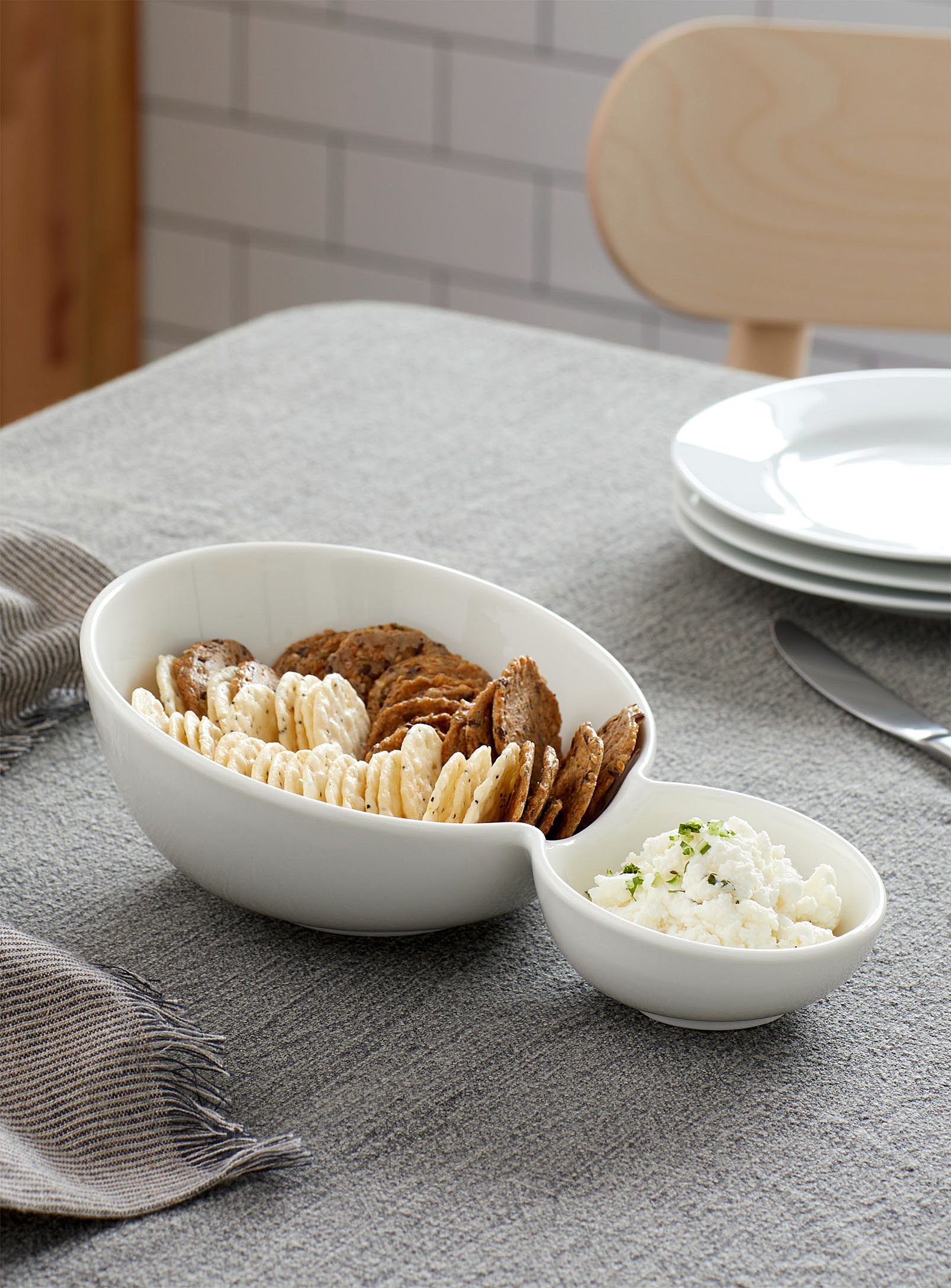 A ceramic double-bowl dish with crackers and dip in it