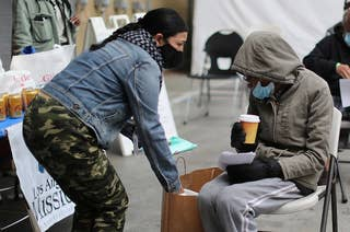 A woman in a gray hoodie sits on a metal chair outdoors and holds a cup of coffee after getting a COVID vaccine at a Los Angles shelter for homeless people.