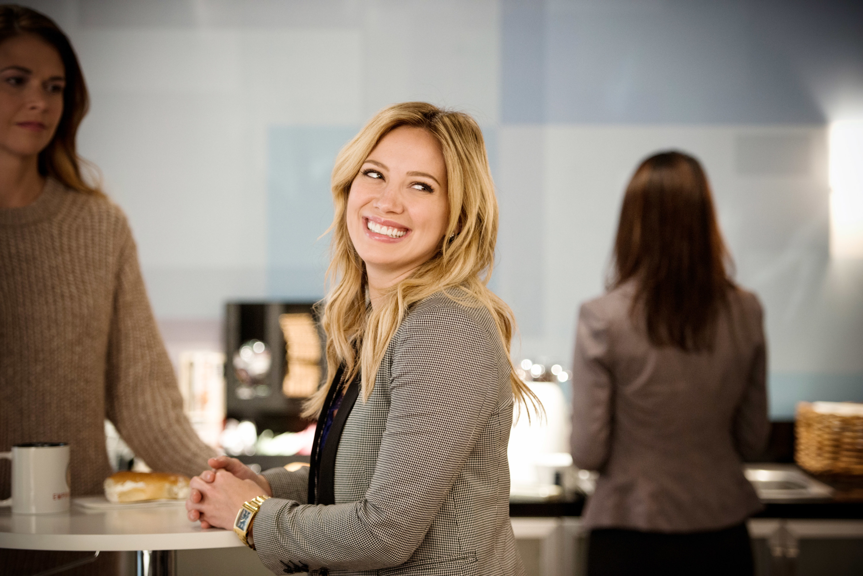 Hilary sits at a countertop and smiles over her shoulder in Younger