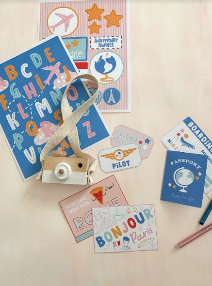 a traveling-themed subscription box with a play passport, camera, and post cards