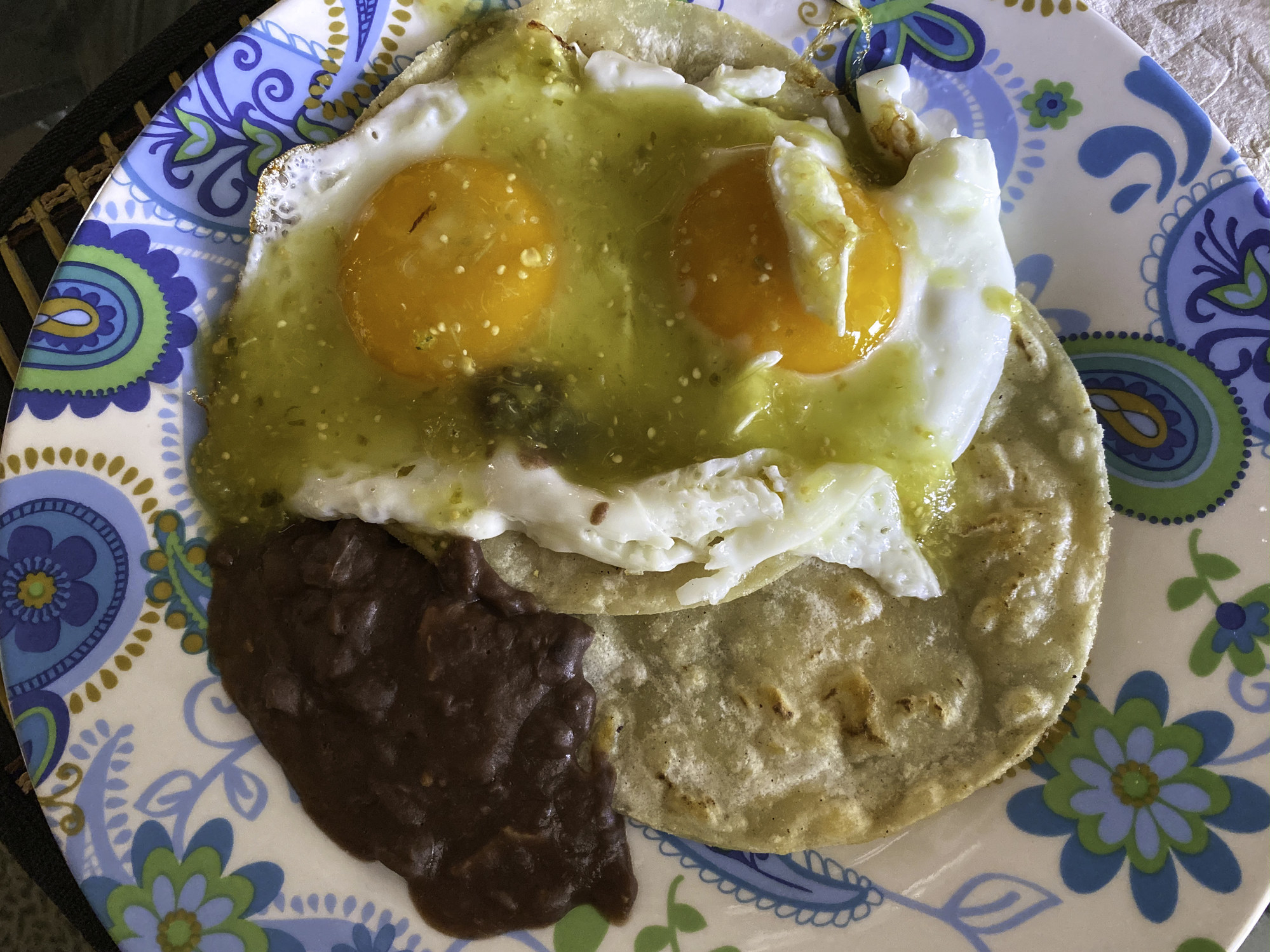 Sunny-side up eggs on top of tortillas and beans.